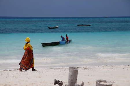 fishman: Zanzibar, Tanzania - January 7, 2016: An African woman in traditional dress walks down the beach. Zanzibar, Tanzania