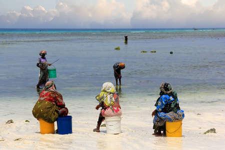 mujeres africanas: Nungwi, Zanzíbar, Tanzania - 11 de enero 2016: Las mujeres africanas en el vestido tradicional en la playa del pueblo de Nungwi. Zanzíbar, Tanzania Editorial