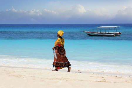 fishman: Zanzibar, Tanzania - January 7, 2016: An African woman in traditional dress with fish walks down the beach. Zanzibar, Tanzania Editorial
