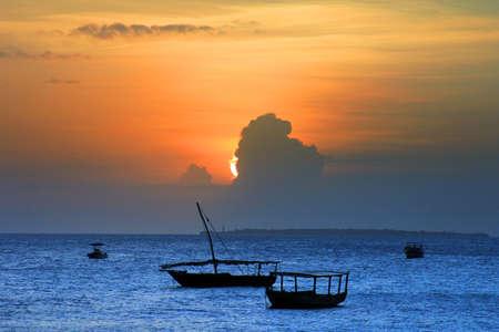 zanzibar: Traditional fishing boats in ocean on sunset. Zanzibar