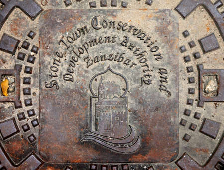 manhole cover: Stoun Town, Tanzania - December 30, 2015:traditional building in the iron manhole cover in Stone Town, Zanzibar