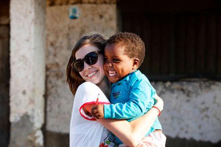 pobreza: Zanzíbar, Tanzania - 8 enero 2016: La mujer joven - un turista de Rusia sostiene Niña africana en sus brazos en Jambiani. Zanzíbar