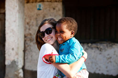 poverty: Zanzibar, Tanzania - January 8, 2016: Young woman - a tourist from Russia holds little African girl in her arms in Jambiani. Zanzibar