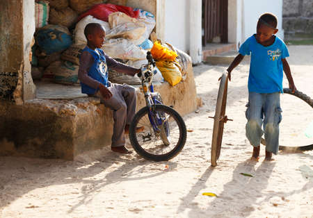 African children: Zanzibar, Tanzania - January 8, 2016: two unknown African boy playing in the street in the village of Jambiani, Zanzibar. Tanzania biên tập