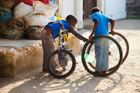 pobreza: Zanzíbar, Tanzania - 8 enero 2016: Dos niño africano desconocido jugando en la calle en el pueblo de Jambiani, Zanzibar. Tanzania