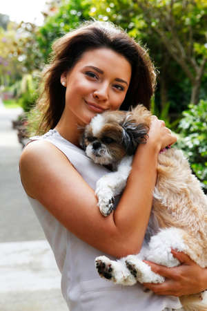 brunet: Portrait of a beautiful brunette with dog outdoors