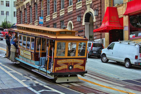san: San Fransisco, CA, USA - September 15, 2011: Passengers ride in a cable car in San Francisco. It is the most popular way to get around the City of San Fransisco which is in service since 1873.