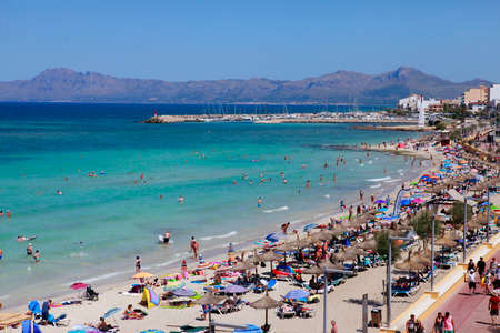expected: Mallorca, Spain - June 29, 2015: The tourists enjoiying their vacation on the beach. Up to 60 mln tourists is expected to visit Spain in year 2015. Editorial
