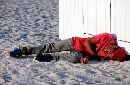 gente durmiendo: Miami Beach, EE.UU. - 5 de mayo de 2013: El dormir sin hogar borracho tumbado en la playa en Miami