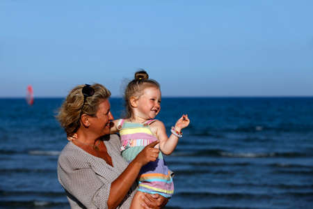 grandmother and children: Grandmother with a little granddaughter on the beach