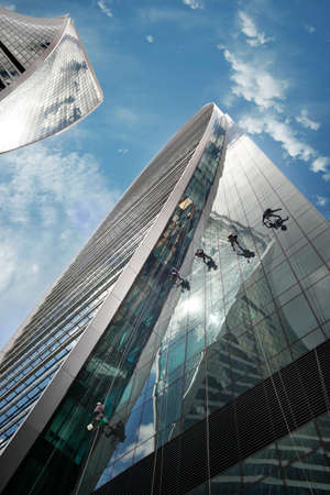 acrophobia: Moscow, Russia - June 10, 2016: Cleaning windows on the side of a high rise building. Moscow City. View of skyscrapers Moscow International Business Center.