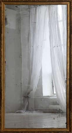 Reflejo de una ventana con cortinas en un antiguo espejo