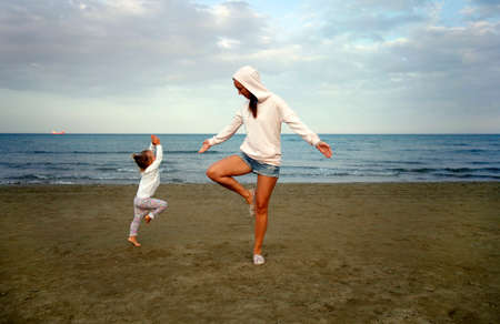 douther: Young woman with small douther practicing yoga on the sea beach at sunset Stock Photo