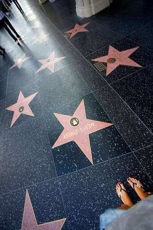 fame: Hollywood, California, United States - September 18, 2011: A person walks along the Hollywood Walk of Fame.