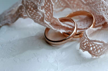 adultery: Wedding rings on a pink tape close-up