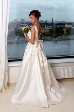 debutante: The beautiful bride with bouquet in room