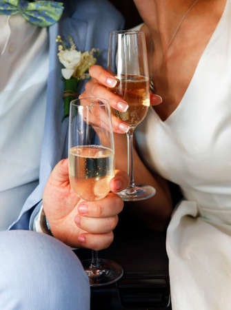 cuff link: Glass of champagne in a hands of the groom and bride