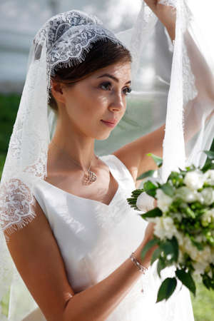 debutante: The beautiful bride with bouquet in park