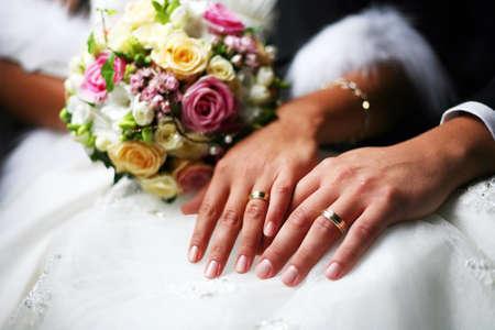 La mano di sposo e la sposa con fedi nuziali Archivio Fotografico - 63171459