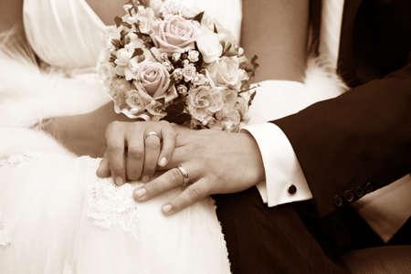 Hand van de bruidegom en de bruid met trouw ringen