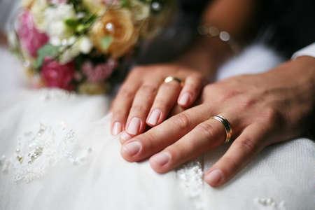 Hand van de bruidegom en de bruid met trouw ringen  Stockfoto