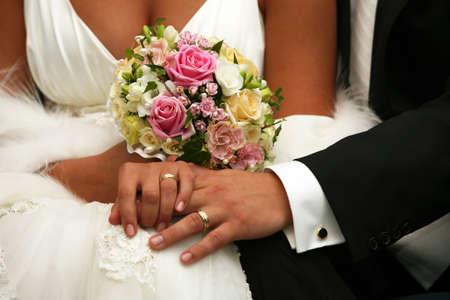 La mano di sposo e la sposa con fedi nuziali