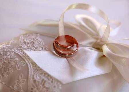 satiny: Wedding rings on a white satiny fabric Stock Photo