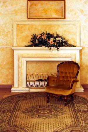 elbowchair: Velvet armchair on a background of a fireplace