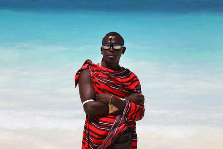 handcarves: Zanzibar, Tanzania - January 5, 2016: Young massai man with colorful traditional clothes, headdress and self made shoes walking through the water on the Nungwi beach. Editorial