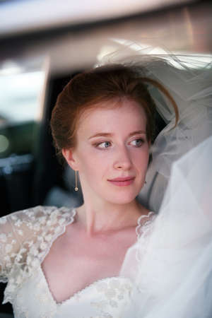 contestant: Portrait of a beautiful bride in a car