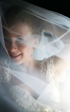 The beautiful bride is closed by a veil photo