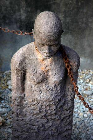 Een standbeeld in Stone Town. Zanzibar die de Afrikaanse slavenhandel uitdokt en rouwt