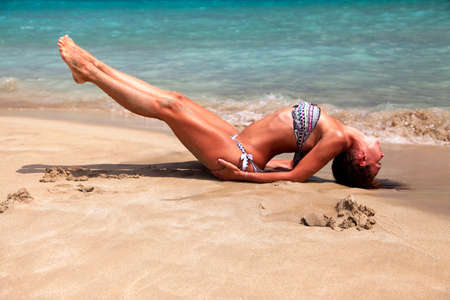 legs crossed at knee: Caucasian woman practicing yoga at seashore