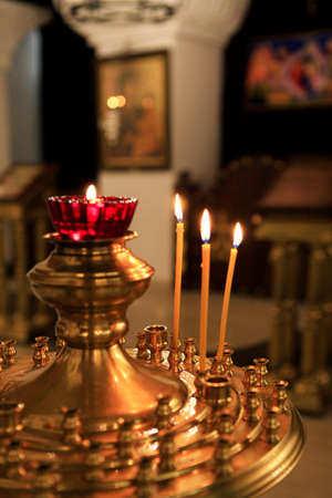 Interior of russian orthodox church. Candles under the ancient icon framed with the gold.