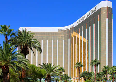 Las Vegas, Nevada, USA - September 19, 2011: Mandalay Bay Hotel and Casino on the Srip in Las Vegas. This view is from the south side with a row of tall palms in the foreground and the afternoon sun illuminating the golden panels of the building. Editorial
