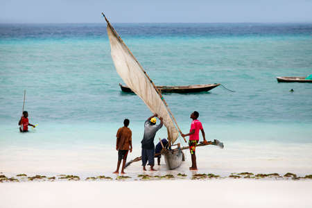 Stone Town (Zanzibar), Tanzania - January 9, 2016: A dhow (traditional sailboat) in the background and a crowded fishing boat and fishman in the foreground in the Indian Ocean just off the island of Zanzibar, Nungwi