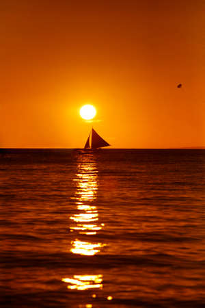 Drifting boat on a sunset. Coast of the Pacific ocean. Island Boracay Stock Photo