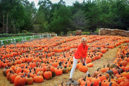 cheerful woman with pumpkin on a farm