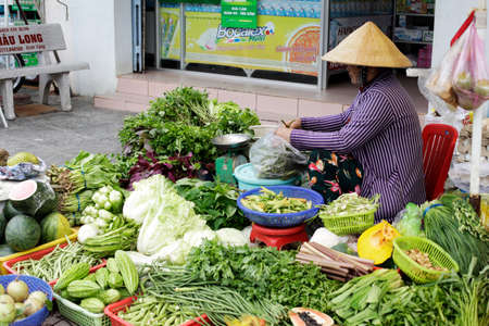 Phu Quoc, Vietnam - January, 11 - 2020: Woman sells vegetables on the street  in Phu Quoc, Vietnam Editorial