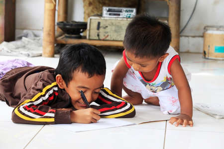 Bali, Indonesia - January 24, 2009: Children of an Indonesian artist paint while sitting on the floor. Bali is famous for talented artists. Bali, Indonesia Editorial
