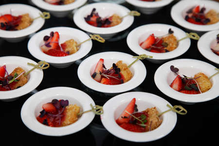 Small piece of breaded tofu with fresh strawberries in a small plate in a buffet Standard-Bild