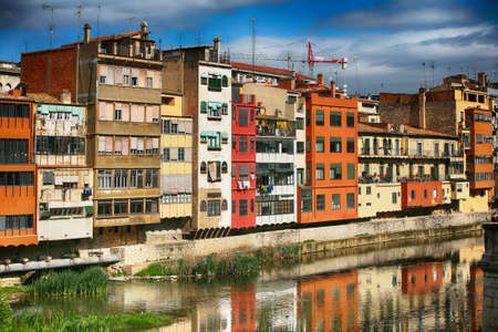 Colorful houses on both sides of the river Onyar with bridge. Beautiful town of Girona, Catalonia, Spain.