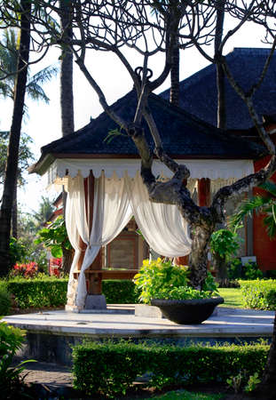 Arbor with white curtains for relaxation or meditation. Bali Island, Indonesia.