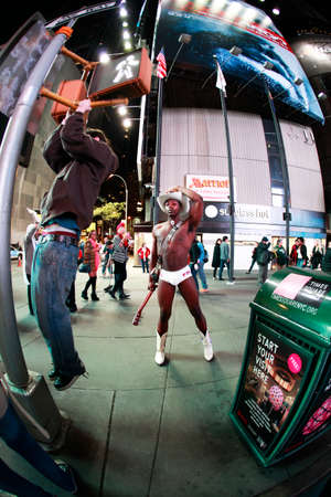 Naked Cowboy showing muscles on Times Square, New York