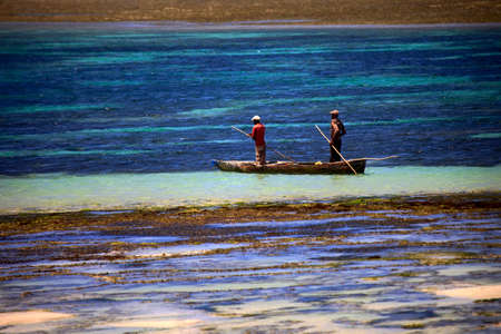 Ukunda, Kenia - January 04 2017: two fishermen in a fishing boat in shallow water. Kenya coast Editorial
