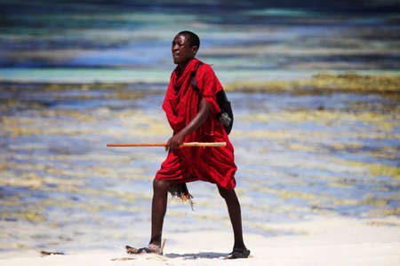 Ukunda, Kenia - January 04 2017: Commercial portrait of young tribal Masai warrior man on hot bright sunny African beach Editorial