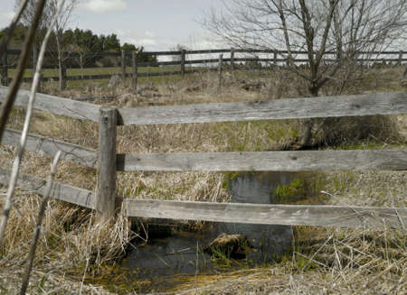 A perimeter fence surrounding a pasture with small stream 版權商用圖片