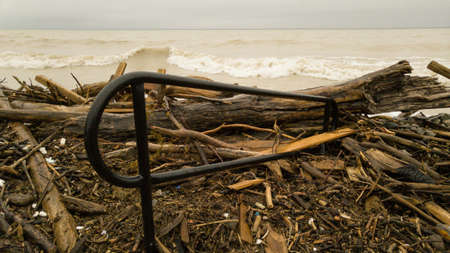 Lake Ontario beach and stairs overwhelmed by lake debris from water surge after constant rain.