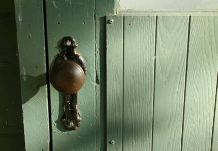 Sunlight casting light and shadows across a wooden door painted green