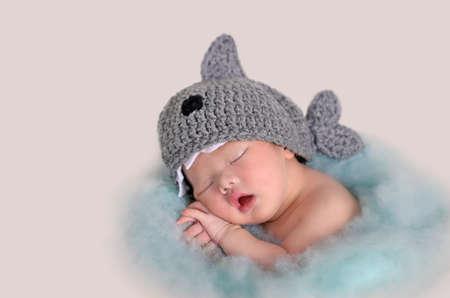 Nettes schlafendes asiatisches Baby in einem Korb mit Wollhaifischhut